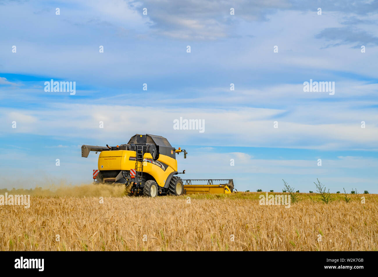 Berlin, Germany - July 05, 2019: View of a moving combine harvester on a field near Berlin under a cloudy sky. Stock Photo