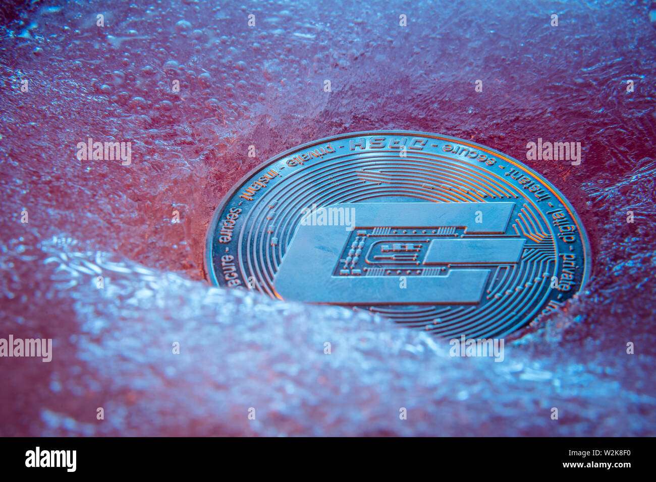 Silver Dash coin, online digital currency frozen in the blue ice. Concept of block chain, market crash. Frozen crypto money, depreciation - Stock Image