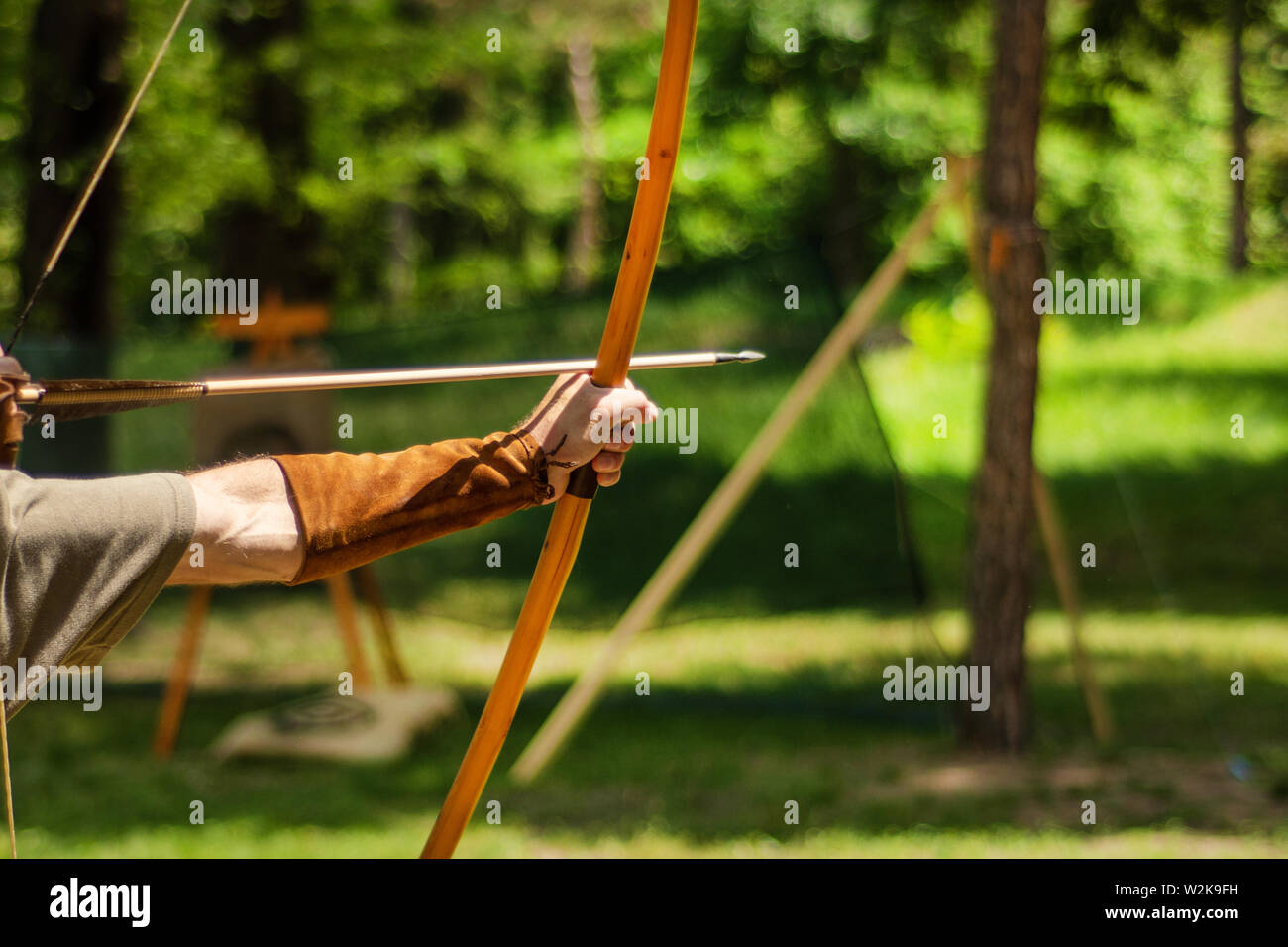 Man medieval archer hand holds his bow with an arrow and aiming at the target outdoor activity in the forest. Medieval sport concept. Close up - Stock Image