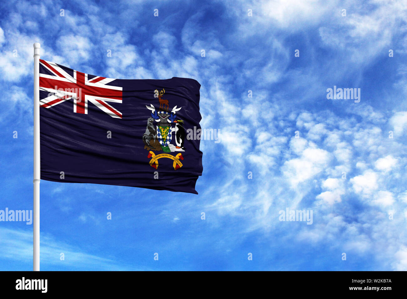 National flag of South Georgia and the South Sandwich Islands on a flagpole in front of blue sky - Stock Image