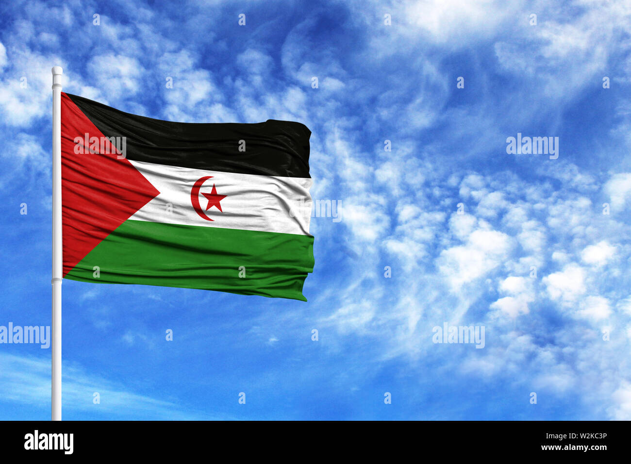 National flag of Western Sahara on a flagpole in front of blue sky - Stock Image