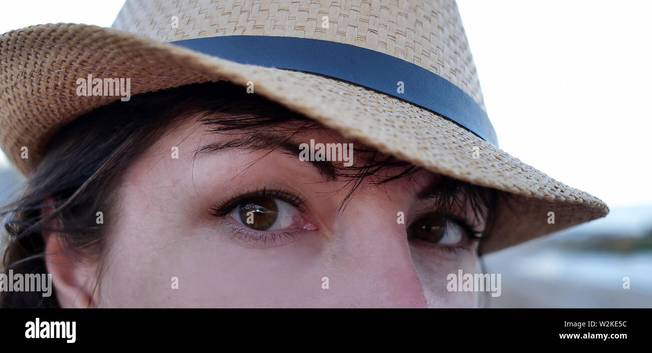Portrait of a brown-eyed brunette in a hat looking straight into the camera with wide eyes Stock Photo