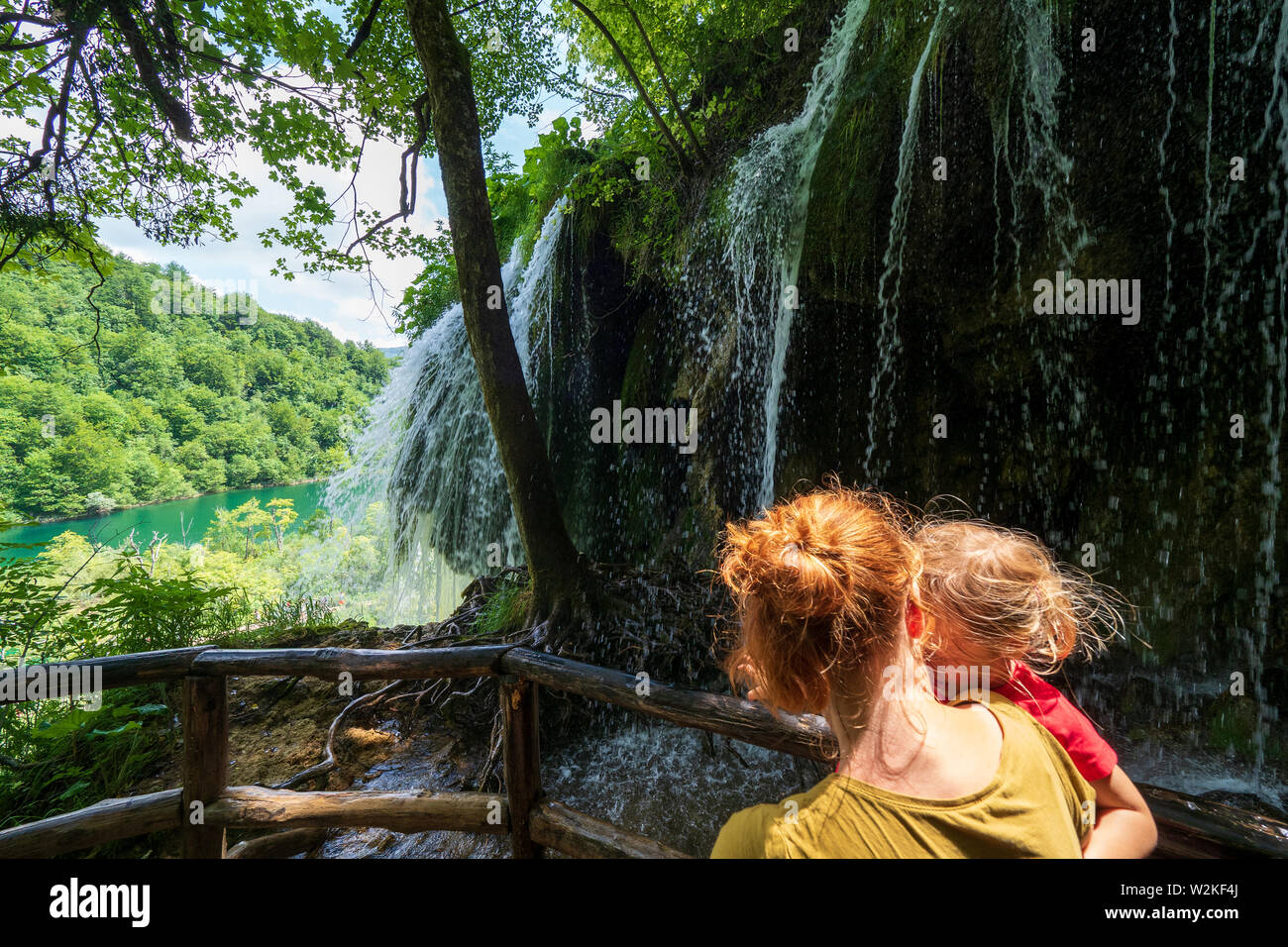 Mother carrying 3 years old girl in front of a rock face where pure fresh water rushing down the edge - Plitvice Lakes National Park in Croatia Stock Photo