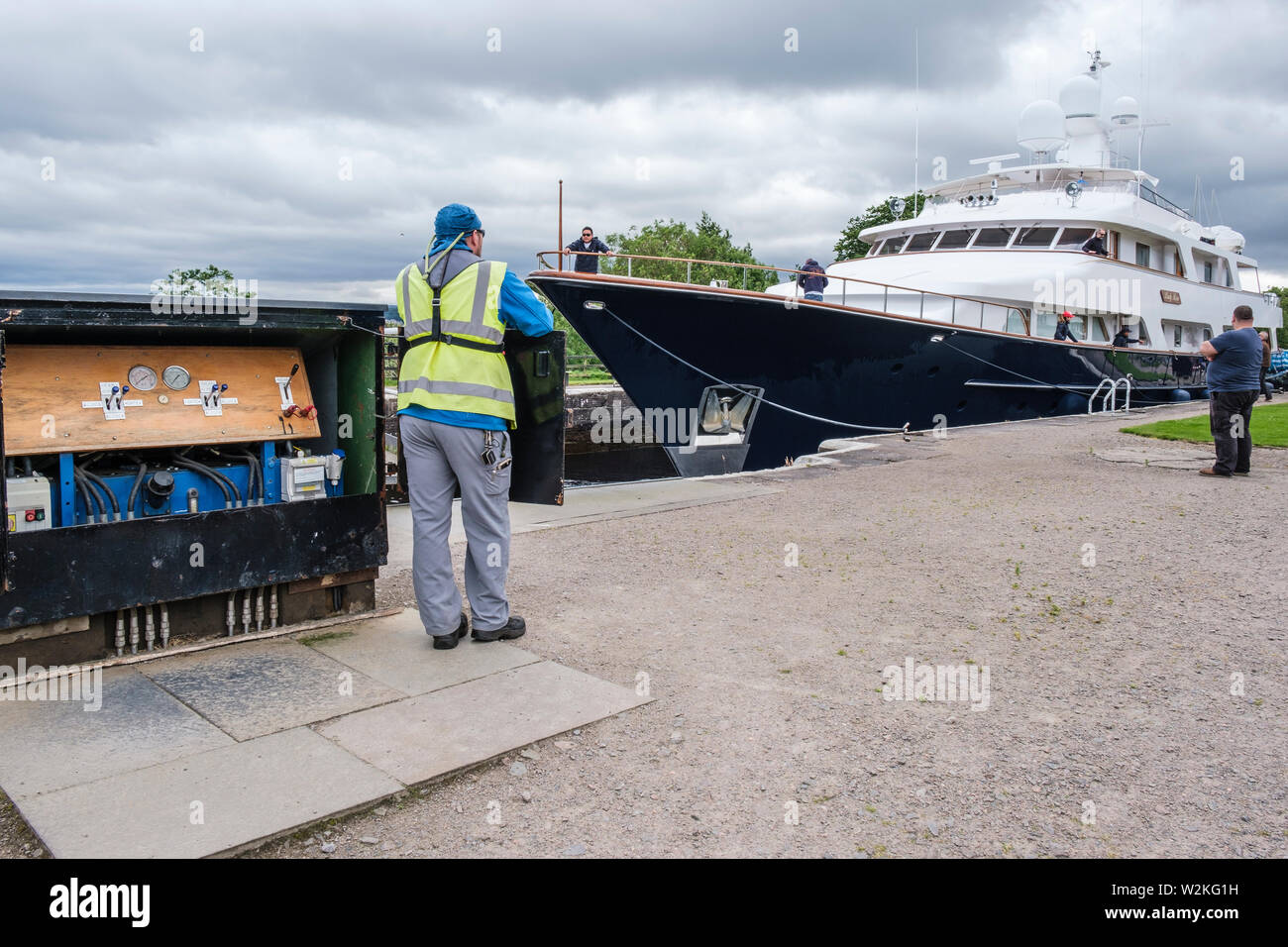 'Lady Rose' passing through Muirtown Locks, Caledonian Canal, Inverness. Lock keeper at lock gate controls. - Stock Image