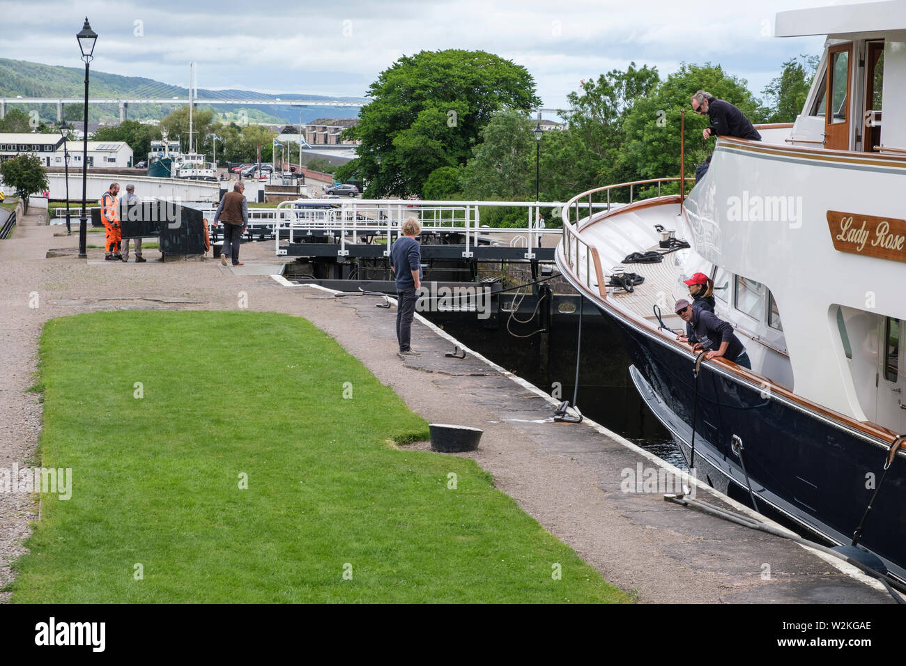 'Lady Rose' passing through Muirtown Locks, Caledonian Canal, Inverness, with Kessock Bridge in distance - Stock Image