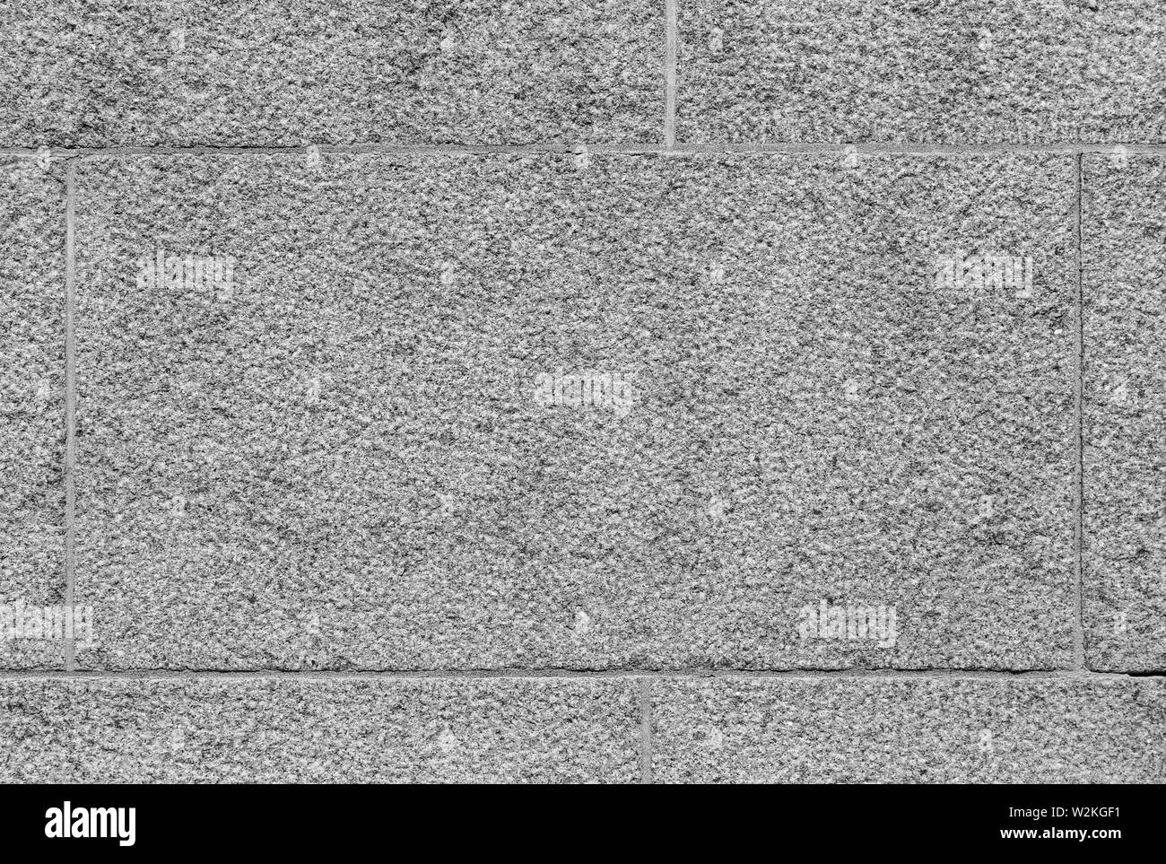 Close-up of part of a bumpy granite block stone wall in black and white. High resolution full frame background texture. Stock Photo