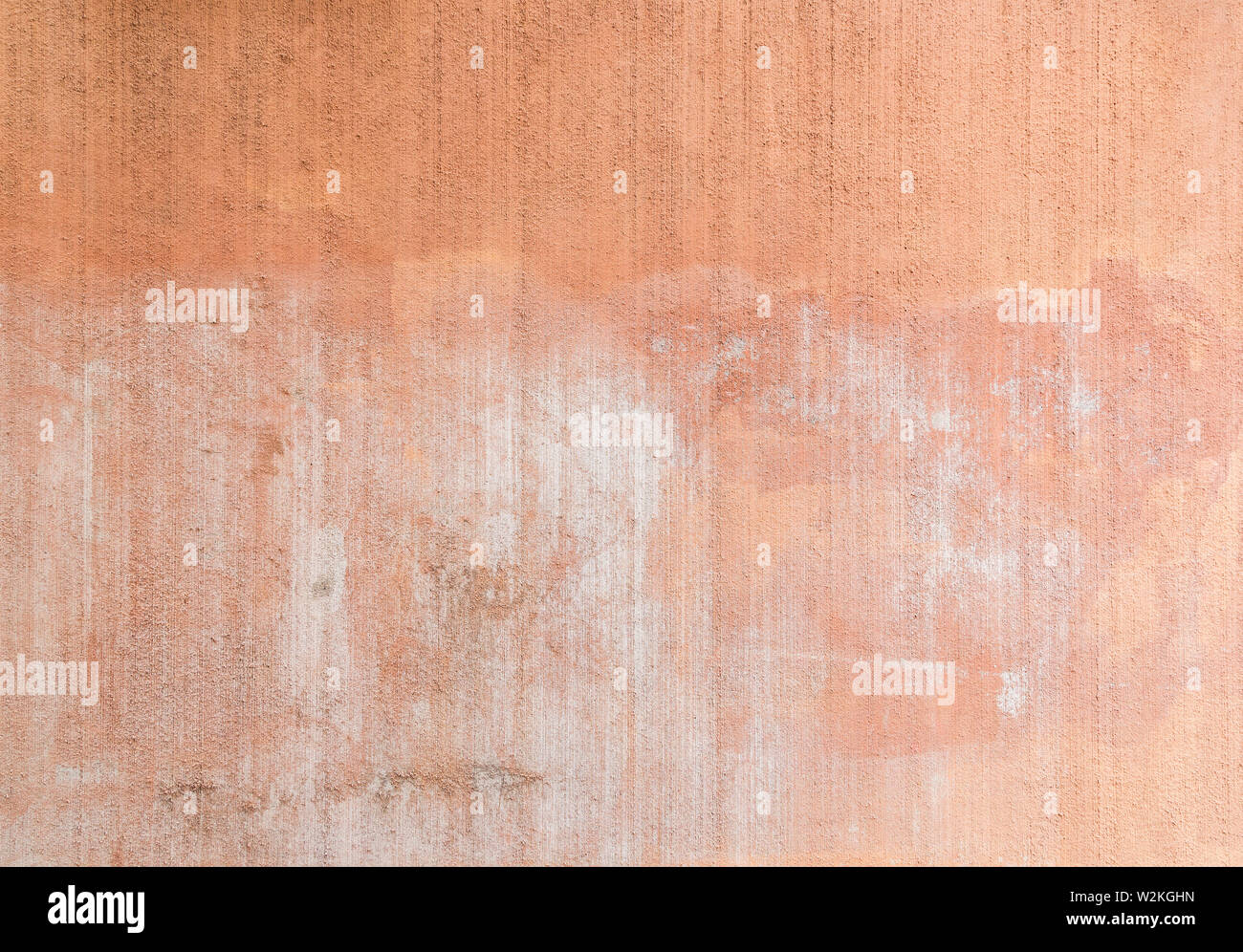 Plastered, painted, weathered, rough and red, orange or peachy concrete or stone wall with marks as a result of graffiti removal. Copy space. Stock Photo