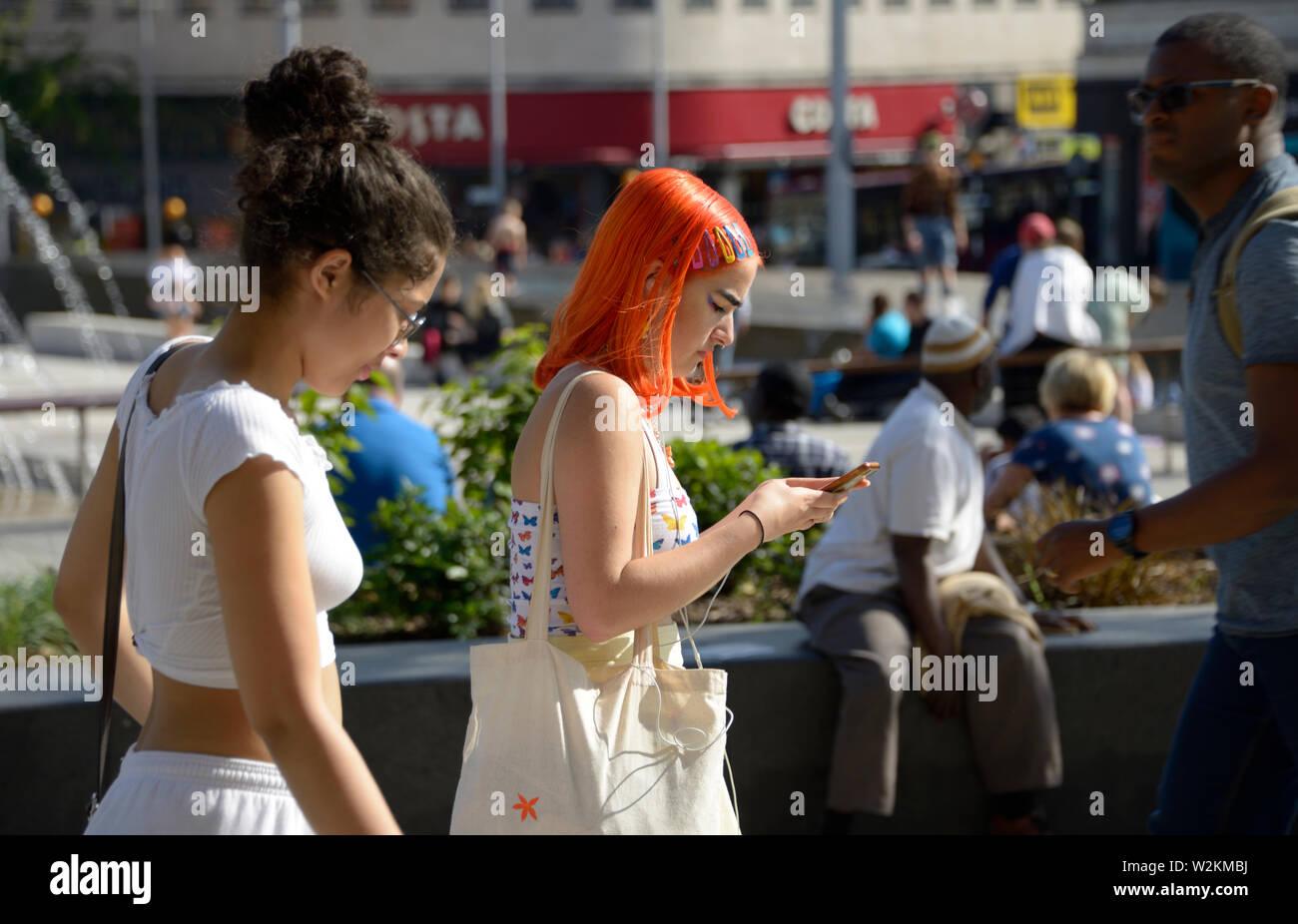 Two girls walking, one with orange hair, on phone - Stock Image
