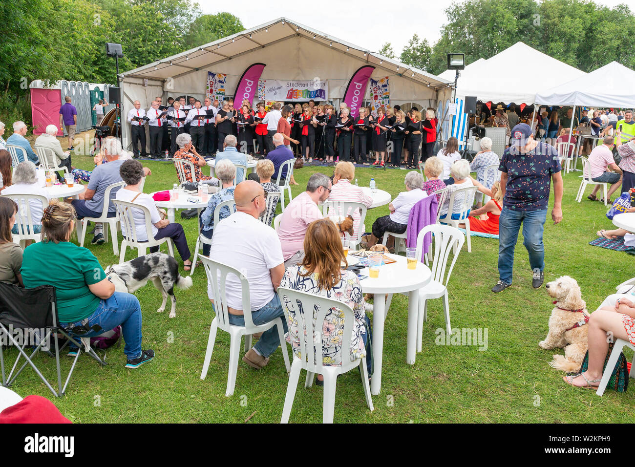 Crowd of seated people watching a choir perform at the main marquee at Stockton Heath Festival 2019 Stock Photo