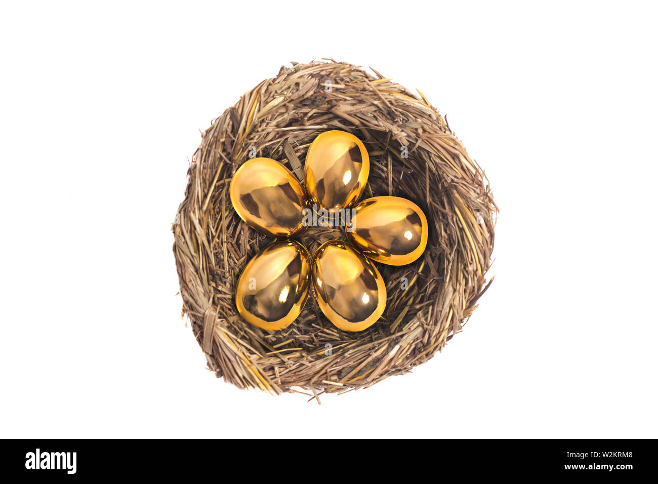 Golden eggs in bird nest on white - Stock Image