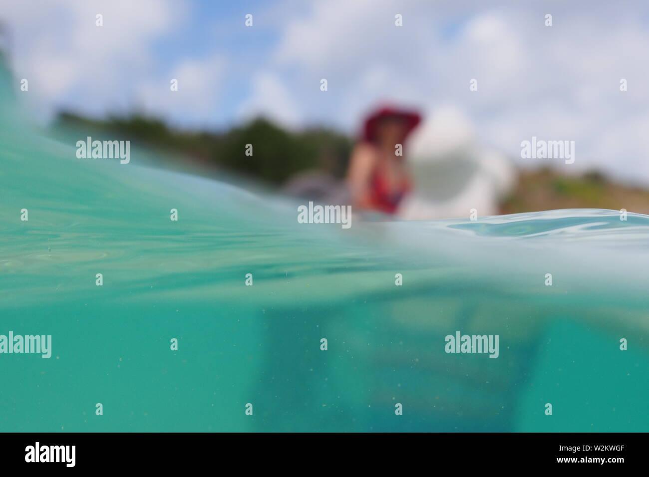 Semi underwater shot of three people swimming, Limestone Bay, Anguilla, BWI. Stock Photo