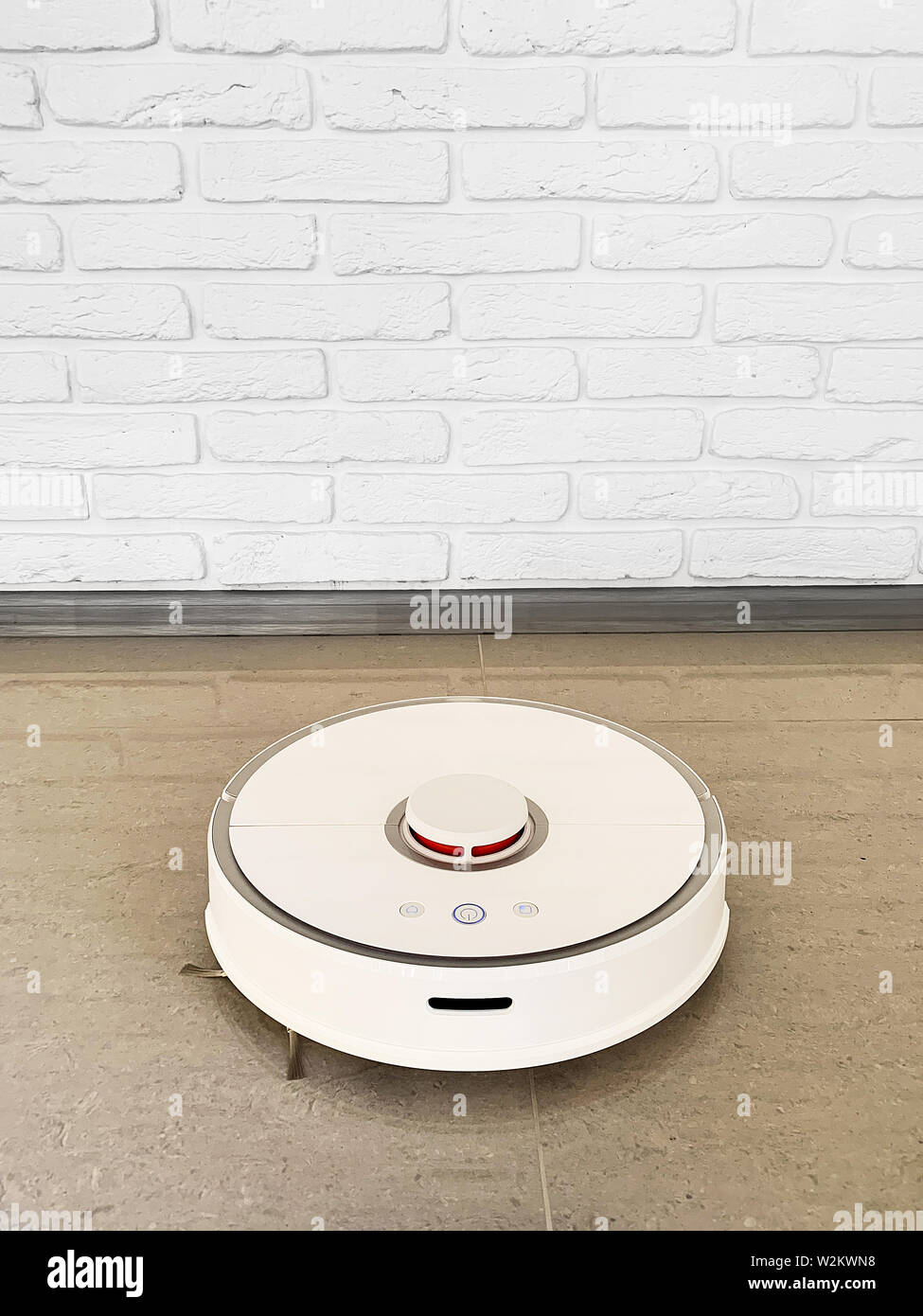 Smart House. Vacuum cleaner robot runs on floor in a living room. - Stock Image
