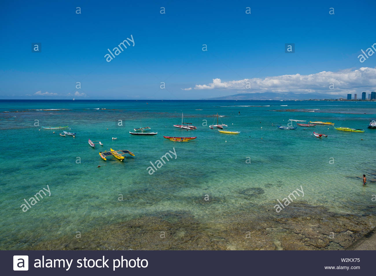 Outrigger canoes anchored offshore, Honolulu, Oahu, Hawaii, USA - Stock Image