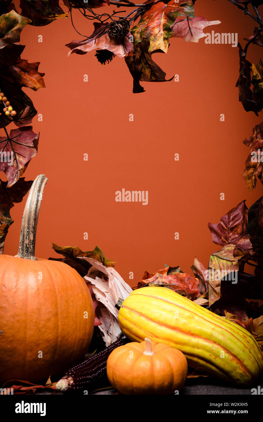 Autumn Vegetables, pumpkins and leaves on a wooden background with orange background Stock Photo