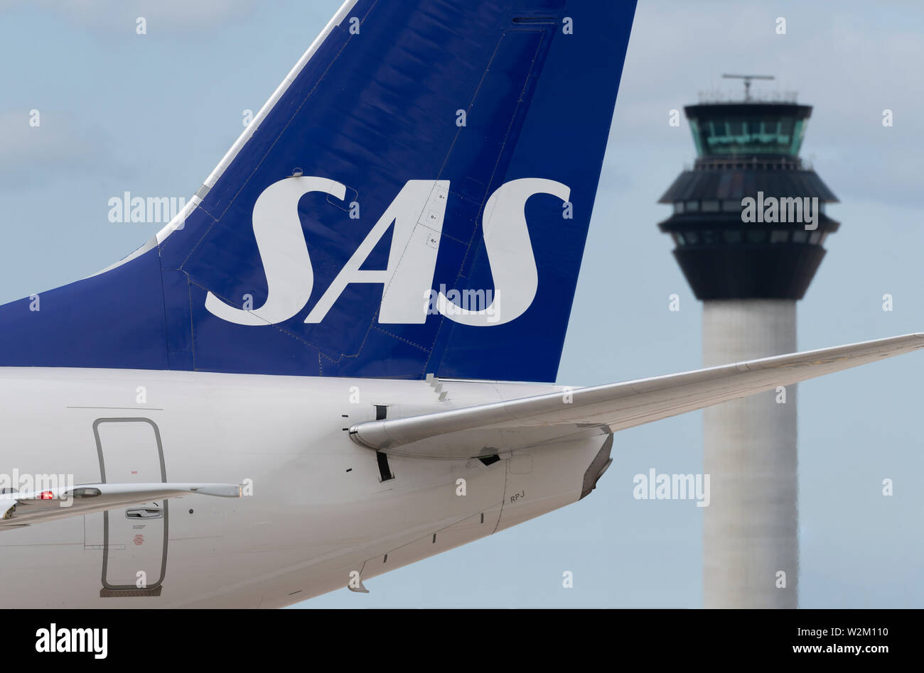 The tailfin of a SAS airliner taxiing along the runway in front of the control tower at Manchester Airport. - Stock Image
