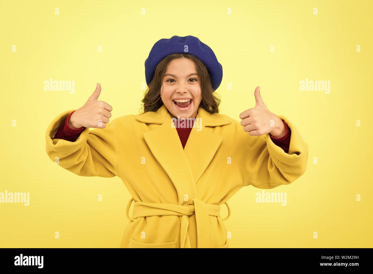 Child promoting something yellow background. Girl show thumbs up gesture. Advertising product. Look at this. Advertisement launching product. Advertisement concept. Place for ad advertisement. Stock Photo