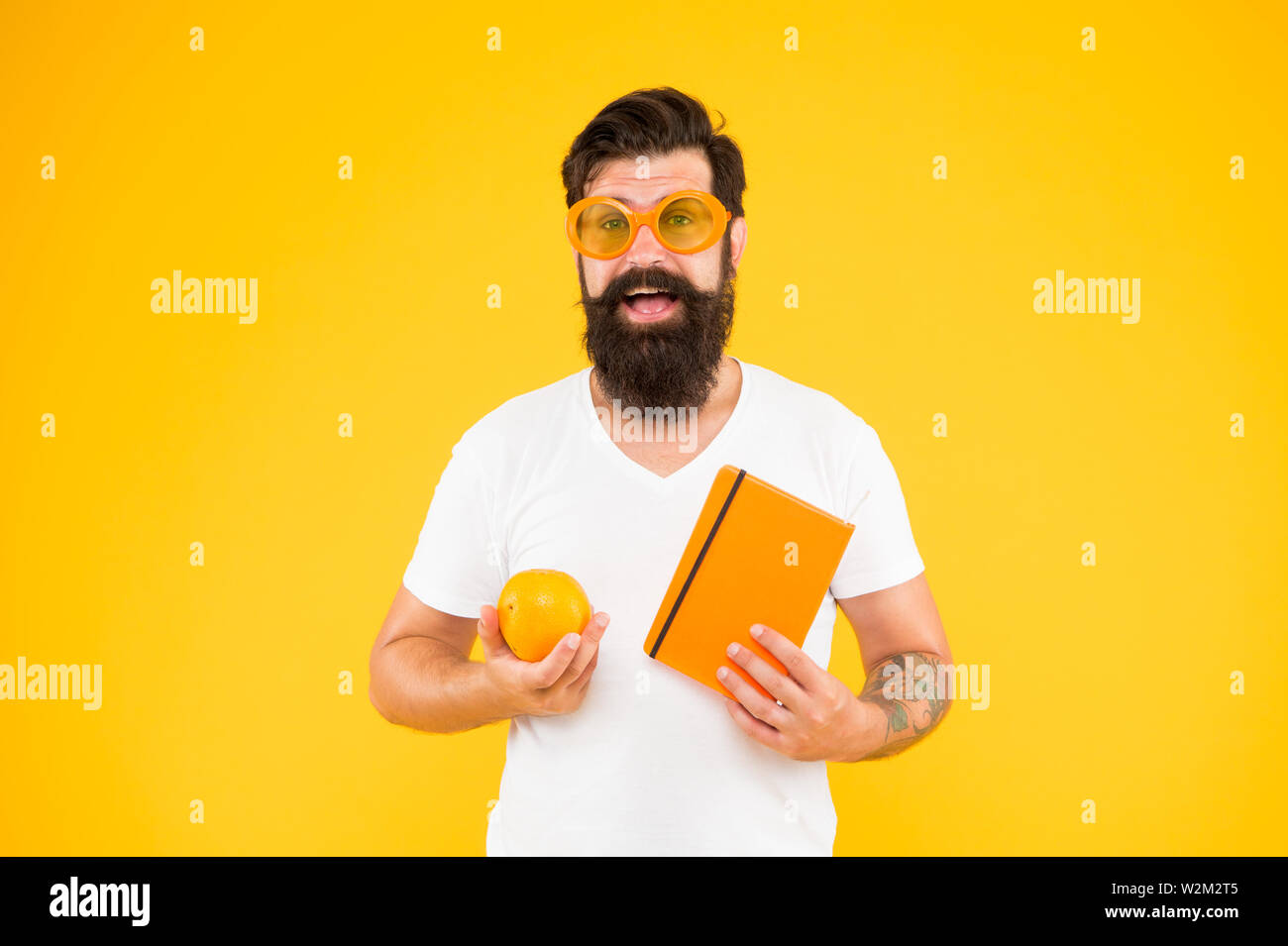 Being proud of geek in you. Geek man. Bearded man in geek glasses holding orange and book on yellow background. Hipster in geek chic style choosing healthy food for brain. - Stock Image