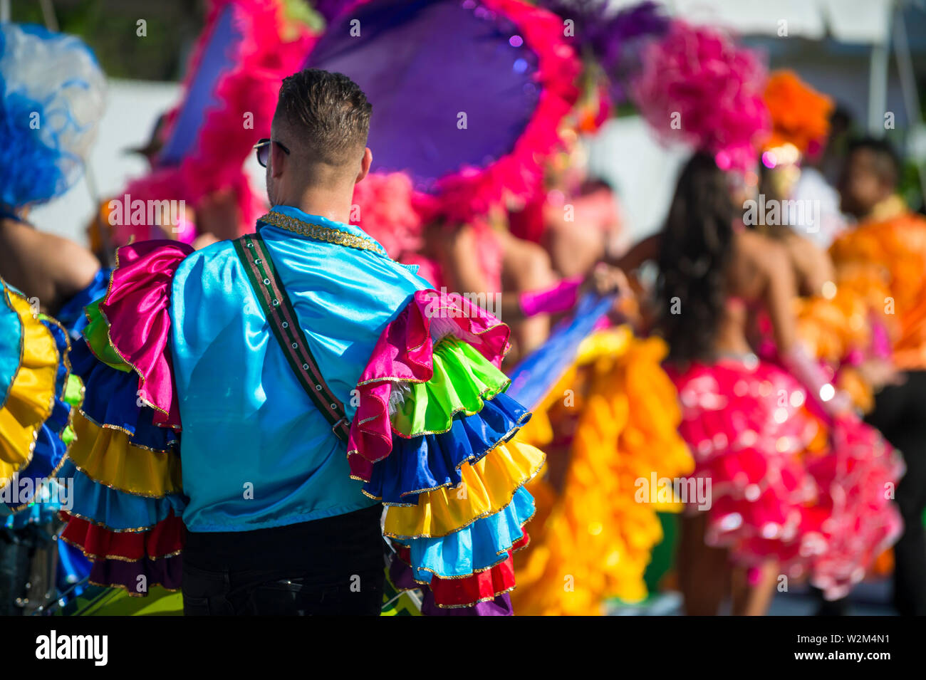 Abstract view of samba dancers in colorful frilled costumes at a daytime Carnival street party in Rio de Janeiro, Brazil - Stock Image