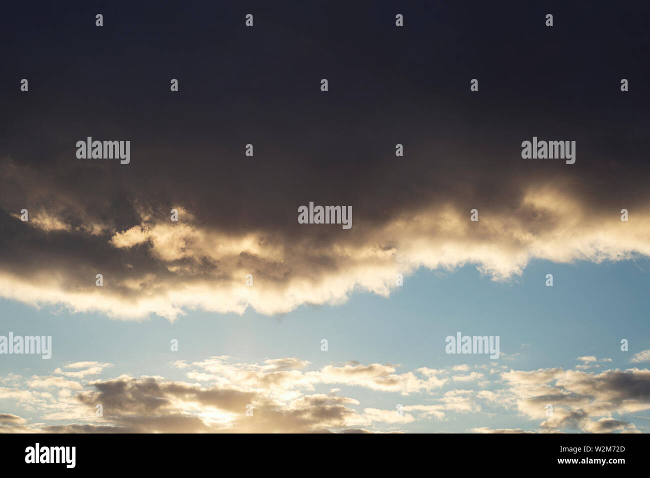 The sky is full of dark clouds in bad weather before a big storm rain. Big black gloomy rain cloud in the sky over the cloudless blue sky . - Stock Image