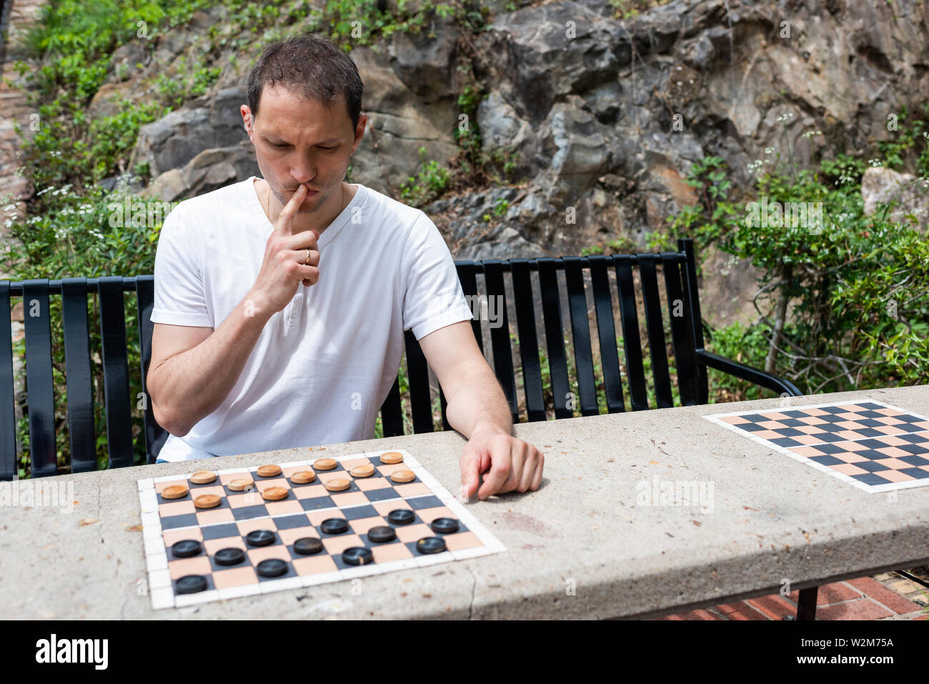 Checkers table in park in Hot Springs, Arkansas with man thinking playing during summer day sitting on bench Stock Photo
