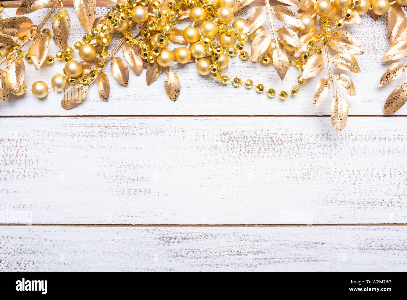 Golden colored Christmas decorations on a white wood background with copy space. Leaves, garland, berries etc. Stock Photo