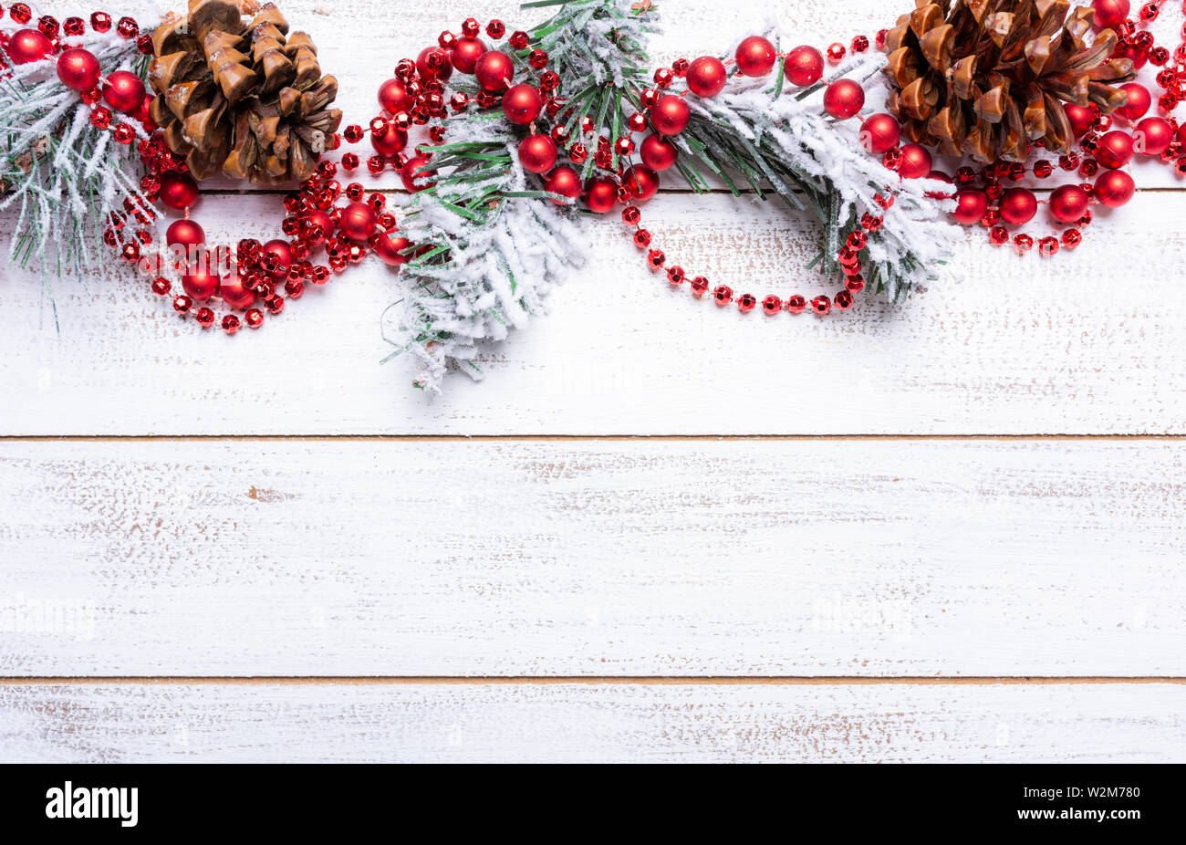 Christmas decorations on a white wood background with copy space. Pine cones, garland, berries and pine branches Stock Photo