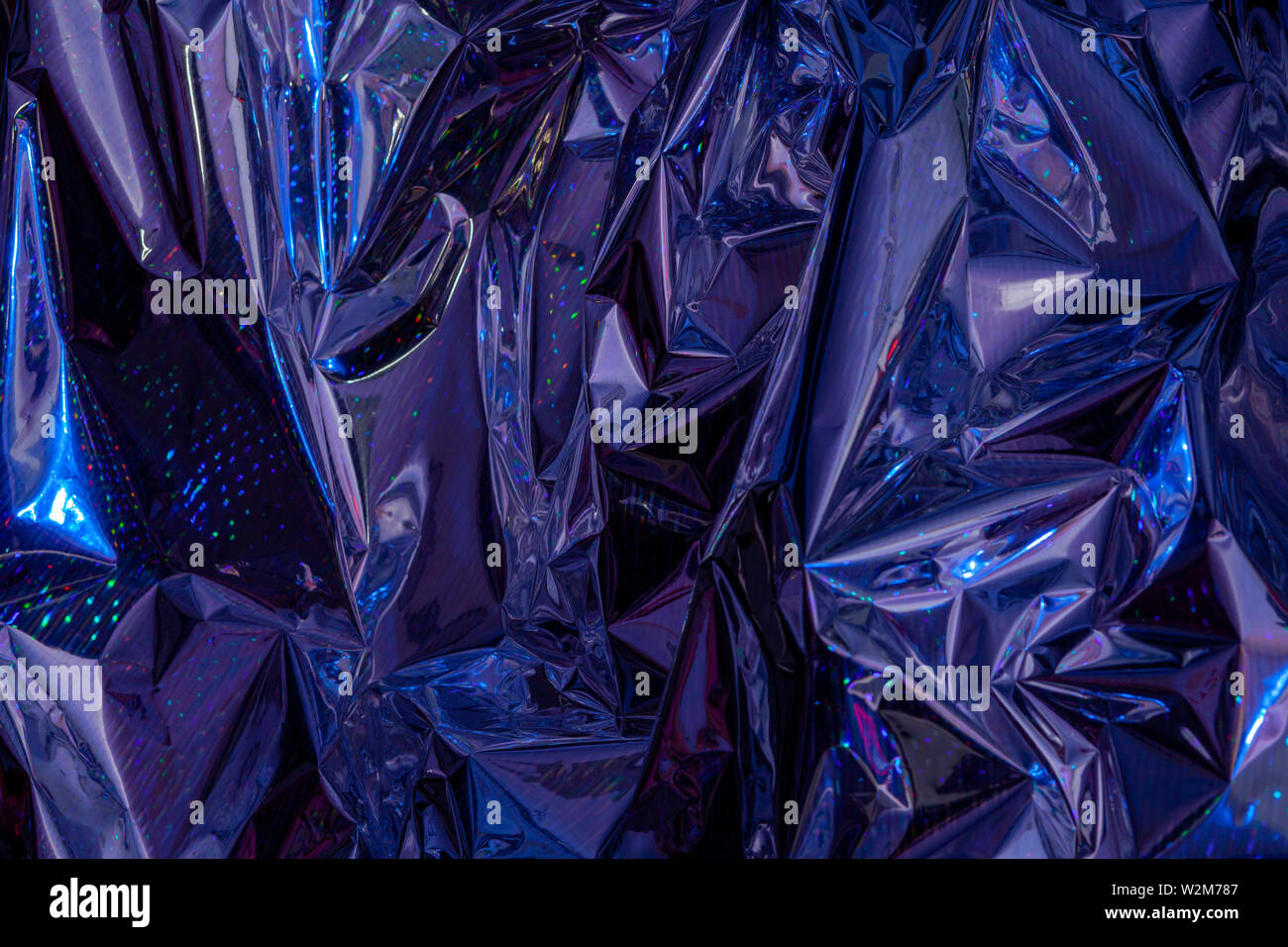 The background of crumpled holographic packaging film with an abstract pattern. Stock Photo