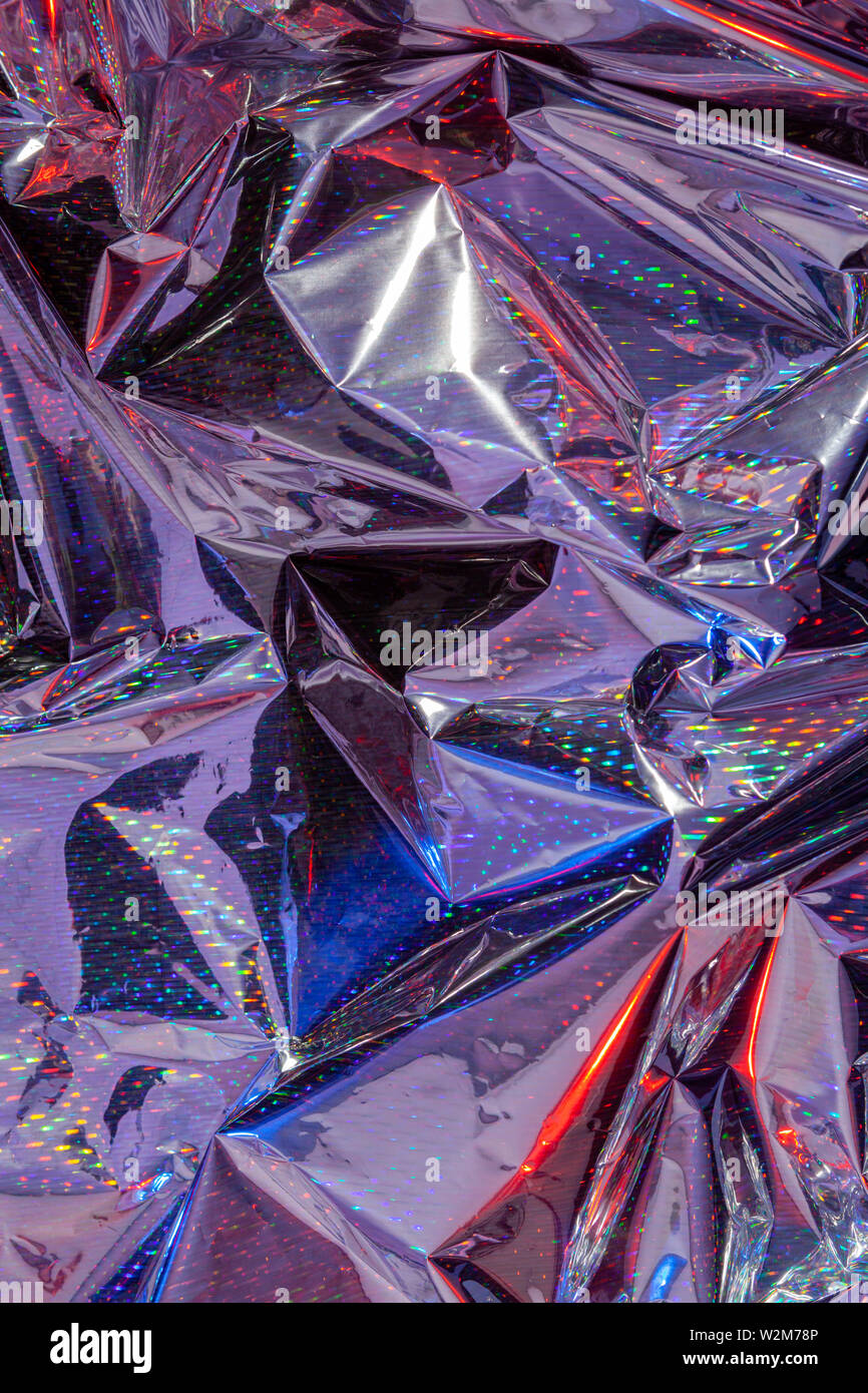 The background of crumpled holographic packaging film with an abstract pattern. - Stock Image