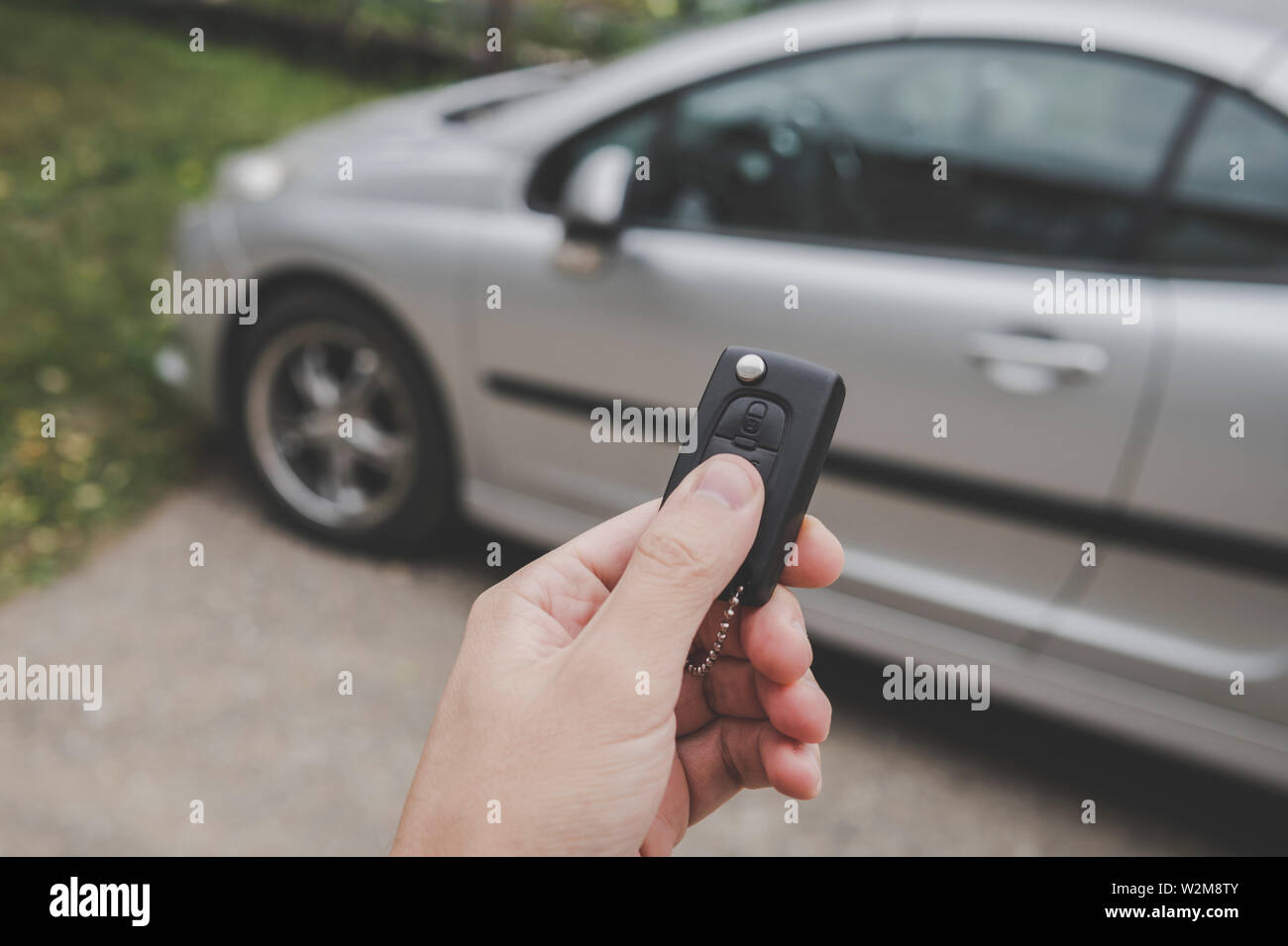 Male car owner switches off the alarm system and unlocks the