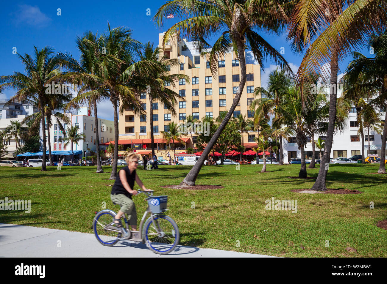 Model released female tourist riding a rental bicycle around Miami's South Beach on a sunny day. - Stock Image