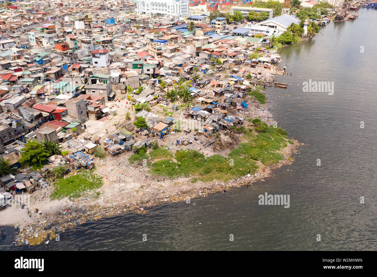 Slums in Manila, a top view. Sea pollution by household waste. Plastic trash on the beach. Stock Photo