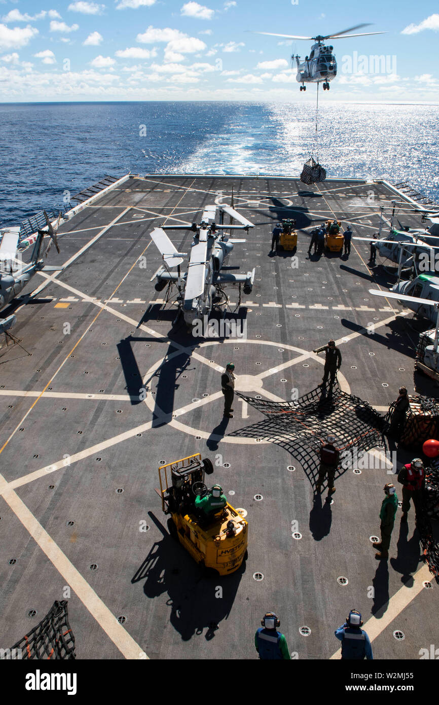 190709-N-DX072-1249 TASMAN SEA (July 9, 2019) An SA-330 Puma helicopter transfers cargo to the amphibious transport dock ship USS Green Bay (LPD 20) during a vertical replenishment with the Military Sealift Command dry cargo and ammunition ship USNS Richard E. Byrd (T-AKE 4). Green Bay, part of the Wasp Amphibious Ready Group, with embarked 31st Marine Expeditionary Unit, is currently participating in Talisman Sabre 2019 off the coast of Northern Australia.  A bilateral, biennial event, Talisman Sabre is designed to improve U.S. and Australian combat training, readiness and interoperability th - Stock Image