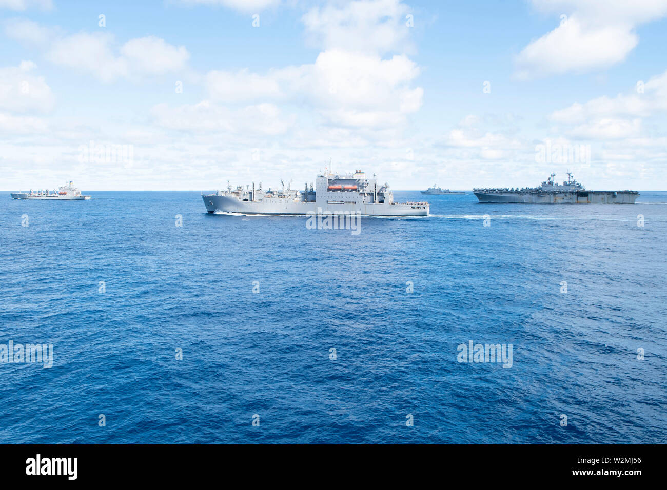 190709-N-DX072-1228 TASMAN SEA (July 9, 2019) The Military Sealift Command fleet replenishment oiler USNS Rappahannock (T-AO 204), the dry cargo and ammunition ship USNS Richard E. Byrd (T-AKE 4), the amphibious dock landing ship USS Ashland (LSD 48), and the amphibious assault ship USS Wasp (LHD 1) transit together during a replenishment-at-sea. Wasp, flagship, Green Bay and Ashland, part of the Wasp Amphibious Ready Group, with embarked 31st Marine Expeditionary Unit, is currently participating in Talisman Sabre 2019 off the coast of Northern Australia.  A bilateral, biennial event, Talisman - Stock Image