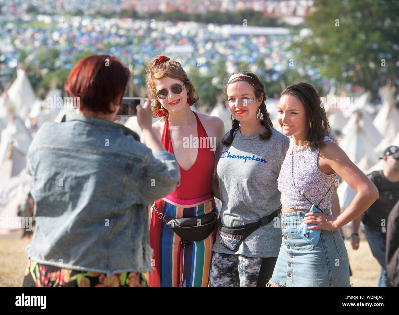 Festival-goers pose for a picture above the Tipi Village at Glastonbury 2019 - Stock Image