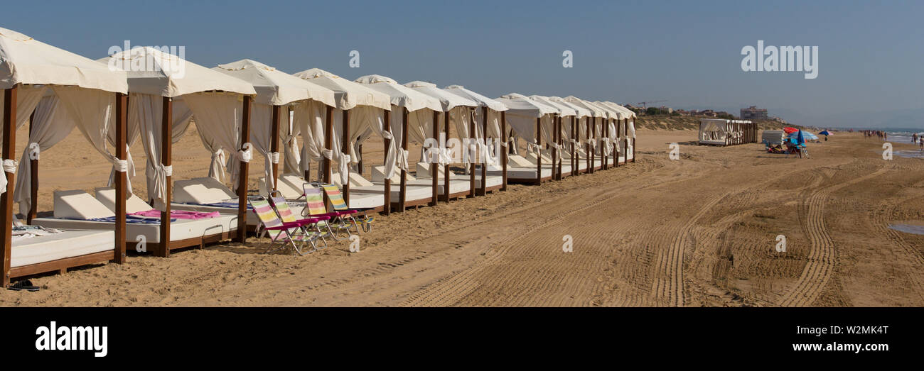 Luxury beach beds for two with white roof and sides like a tent panoramic view - Stock Image