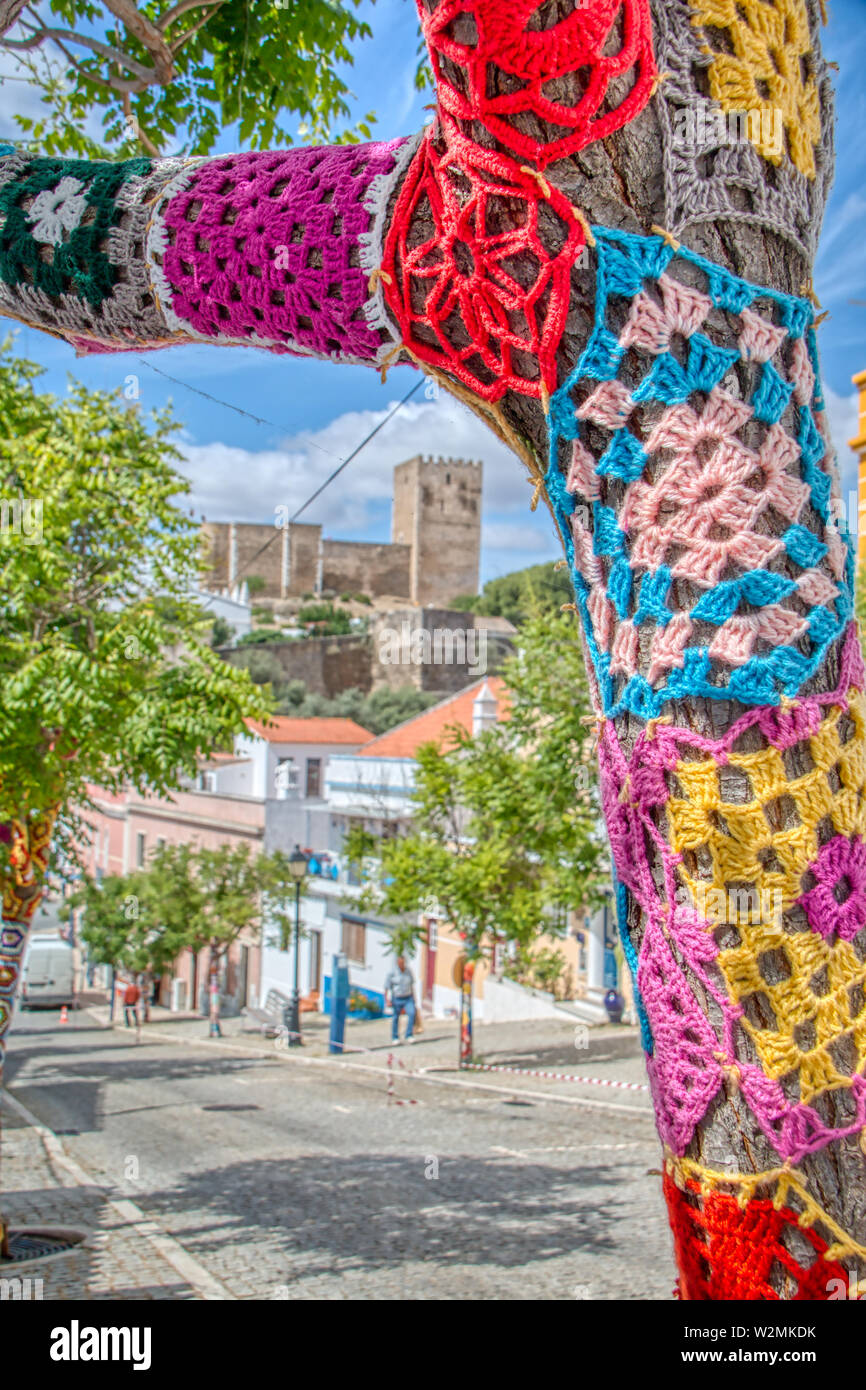 Mertola, Portugal - May 18, 2019: Trees decorated with colorful crochet patchwork on a holiday in the town of Mertola, a very beautiful city in the Po Stock Photo