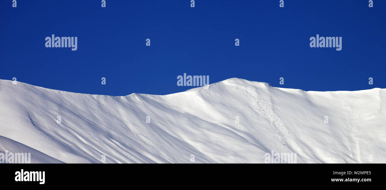 Panoramic view on snowy off-piste slope and blue clear sky in nice winter day. Caucasus Mountains, Georgia, region Gudauri. - Stock Image