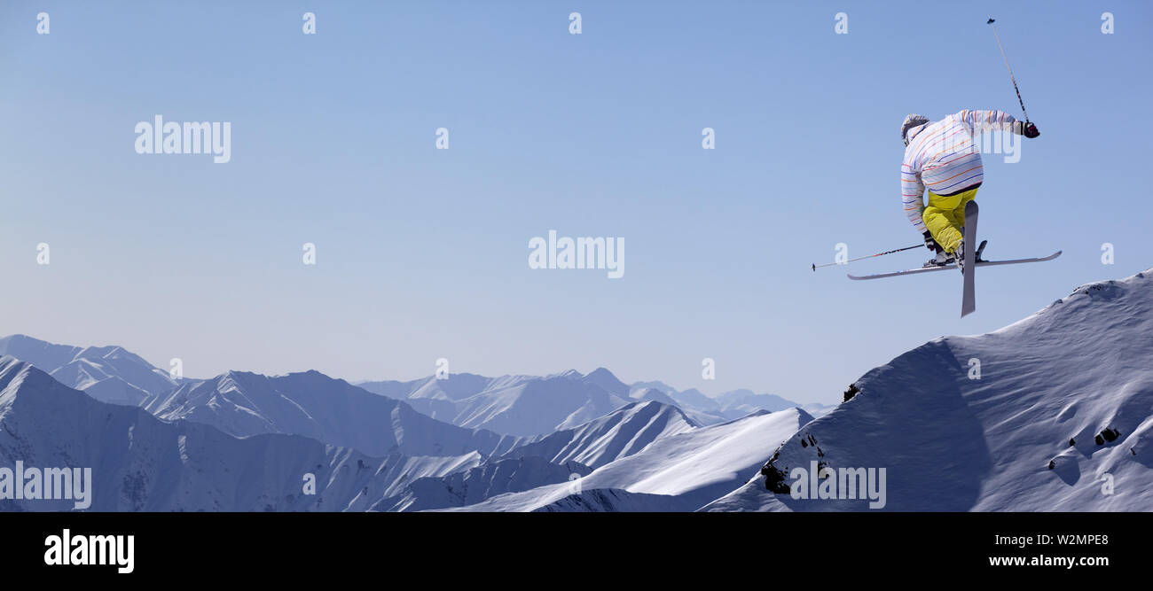 Freestyle ski jumper with crossed skis in snowy mountains at sunny winter day. Panoramic view. - Stock Image