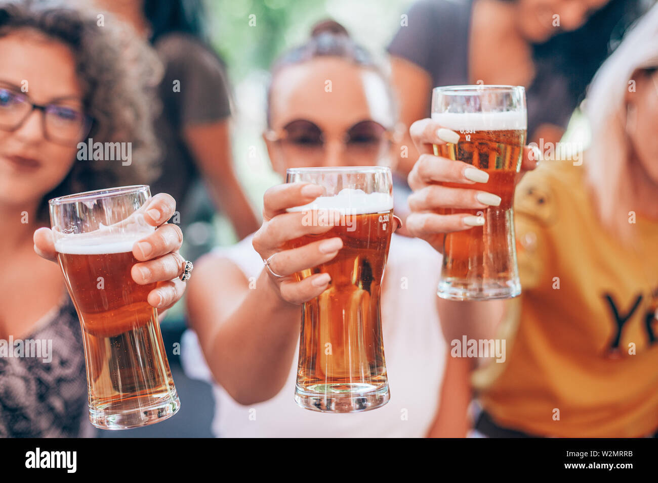 Happy group of best friends drinking light beer - Friendship concept with young female friends enjoying time and having genuine fun at outdoor nature - Stock Image
