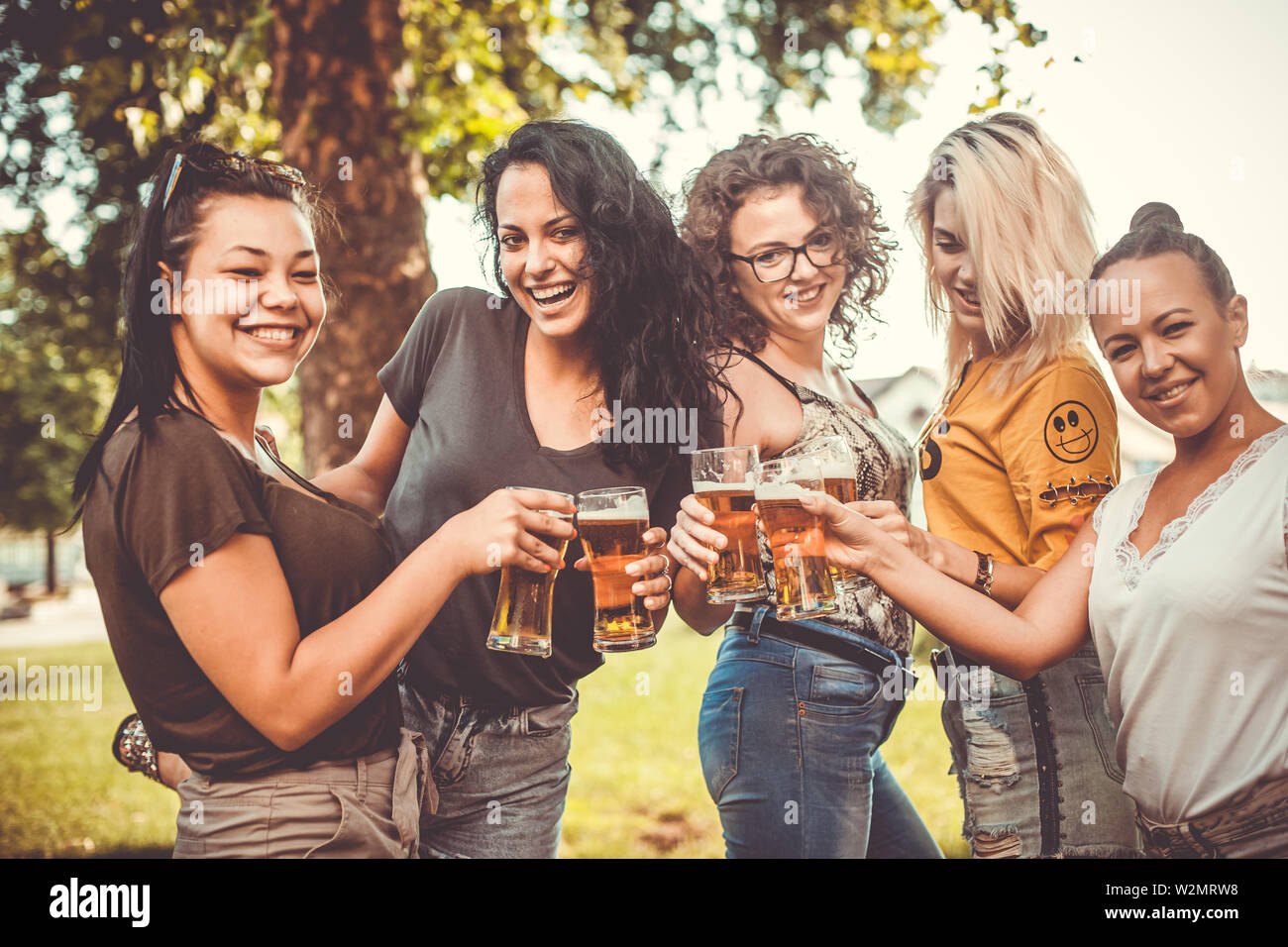 Group of best female friends drinking light beer - Friendship concept with young female friends enjoying time and having genuine fun at outdoor nature - Stock Image