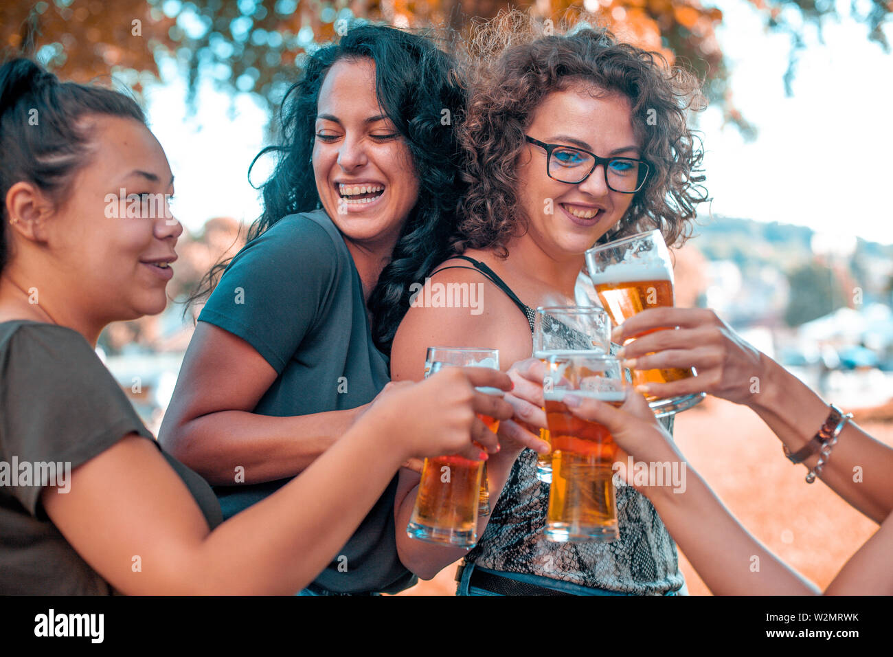 Happy group of best female friends drinking light beer - Friendship concept with young female friends enjoying time and having genuine fun at outdoor - Stock Image