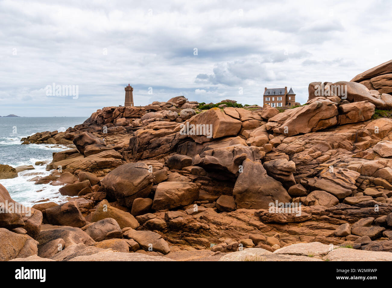 Beautiful rocky landscape in the coast of Brittany, Ploumanac'h lighthouse against sky. Stock Photo