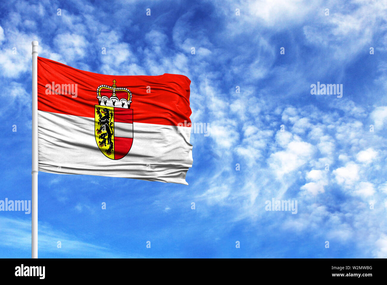 National flag of Salzburg on a flagpole in front of blue sky - Stock Image