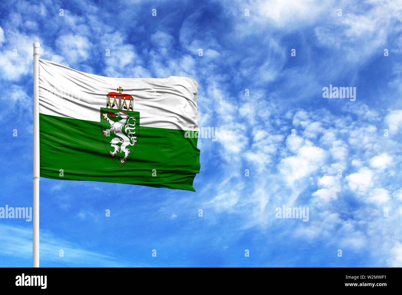 National flag of Styria on a flagpole in front of blue sky - Stock Image