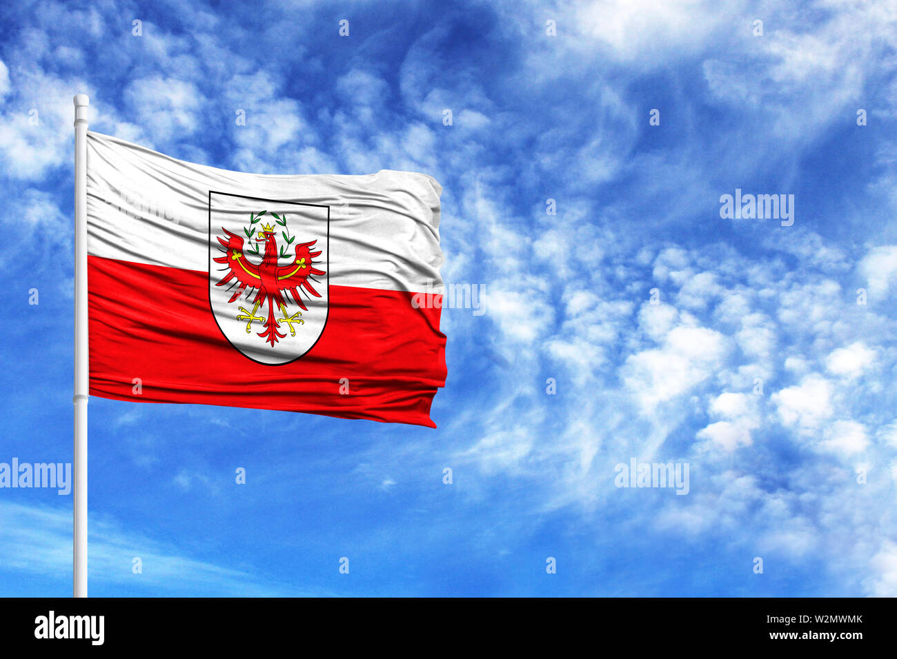 National flag of Tyrol on a flagpole in front of blue sky - Stock Image