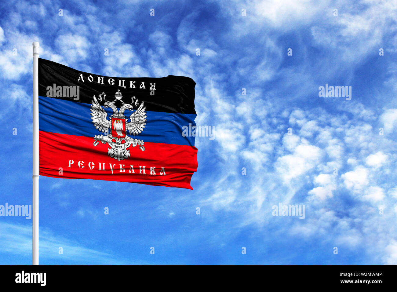 National flag of the Donetsk People's Republic on a flagpole in front of blue sky - Stock Image