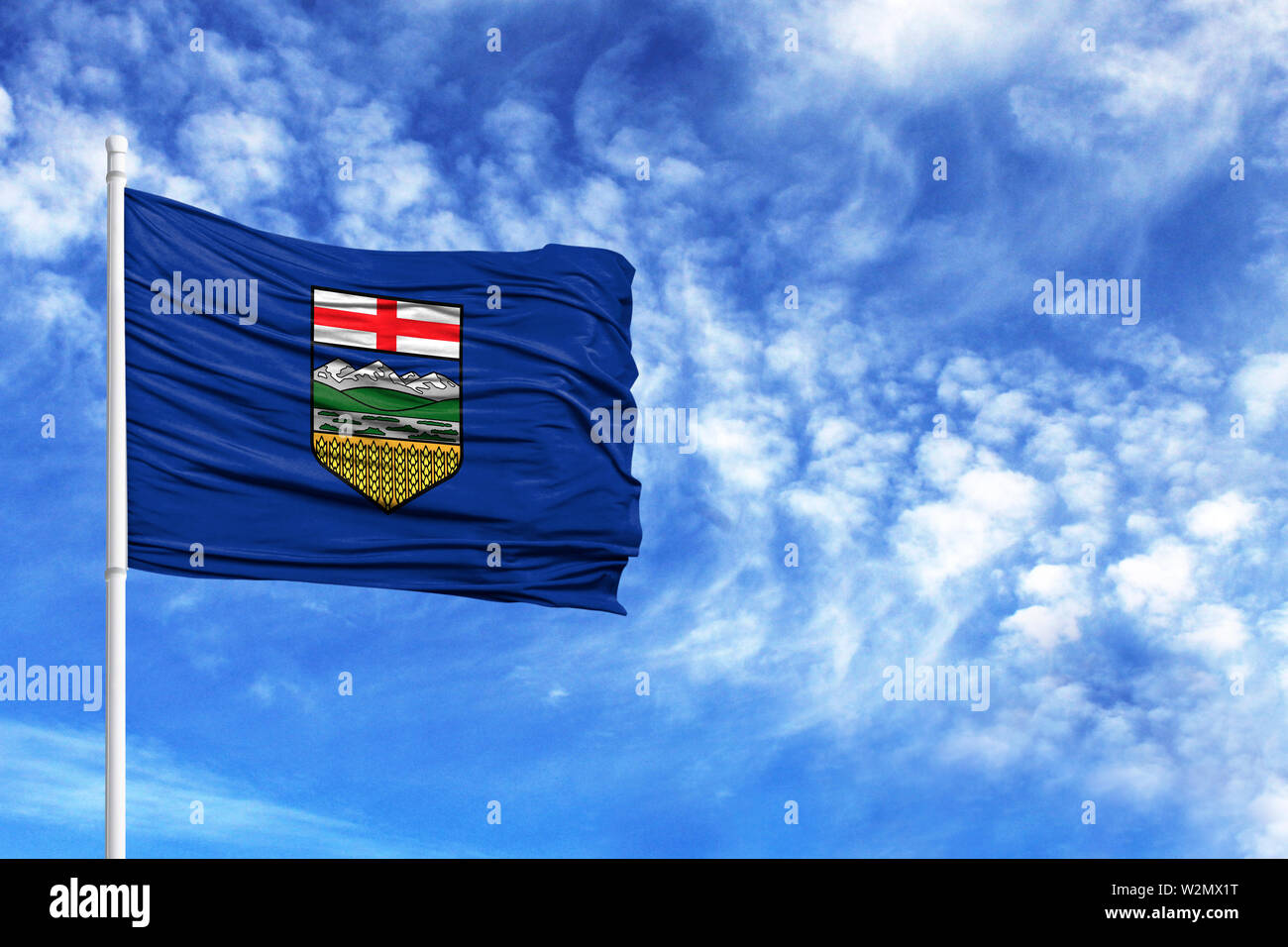 National flag of Alberta on a flagpole in front of blue sky - Stock Image