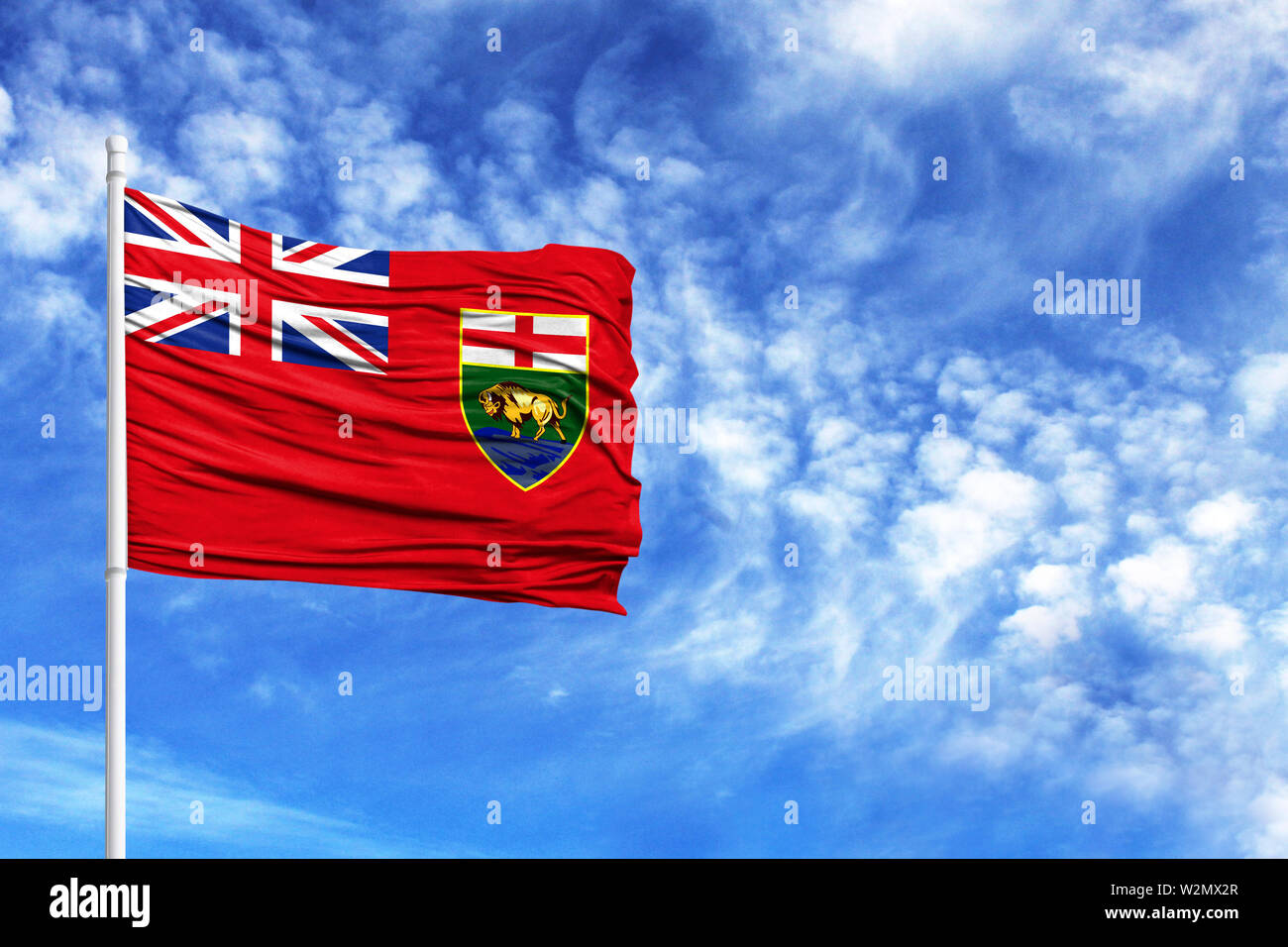National flag of Manitoba on a flagpole in front of blue sky - Stock Image
