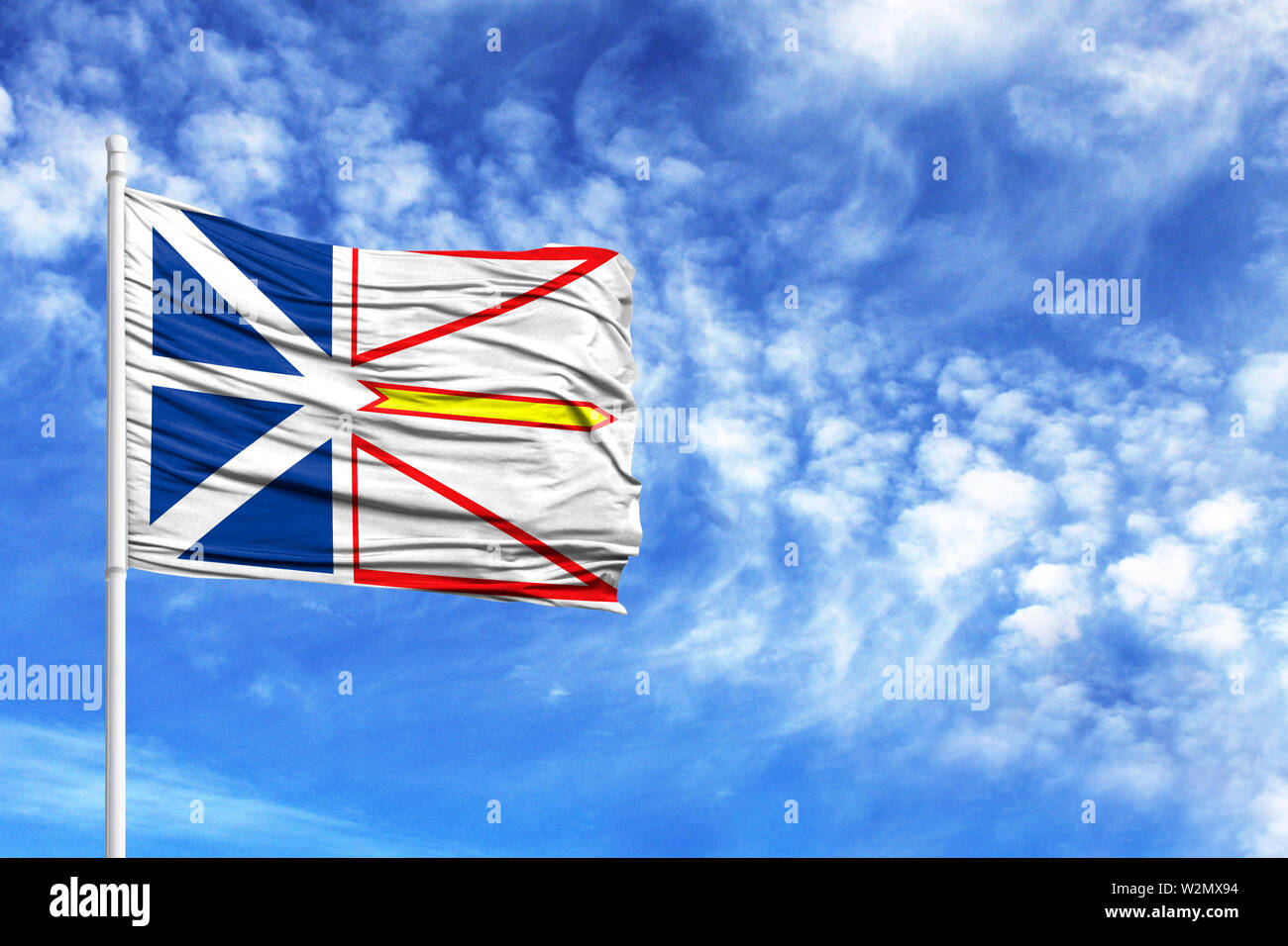 National flag of Newfoundland and Labrador on a flagpole in front of blue sky - Stock Image