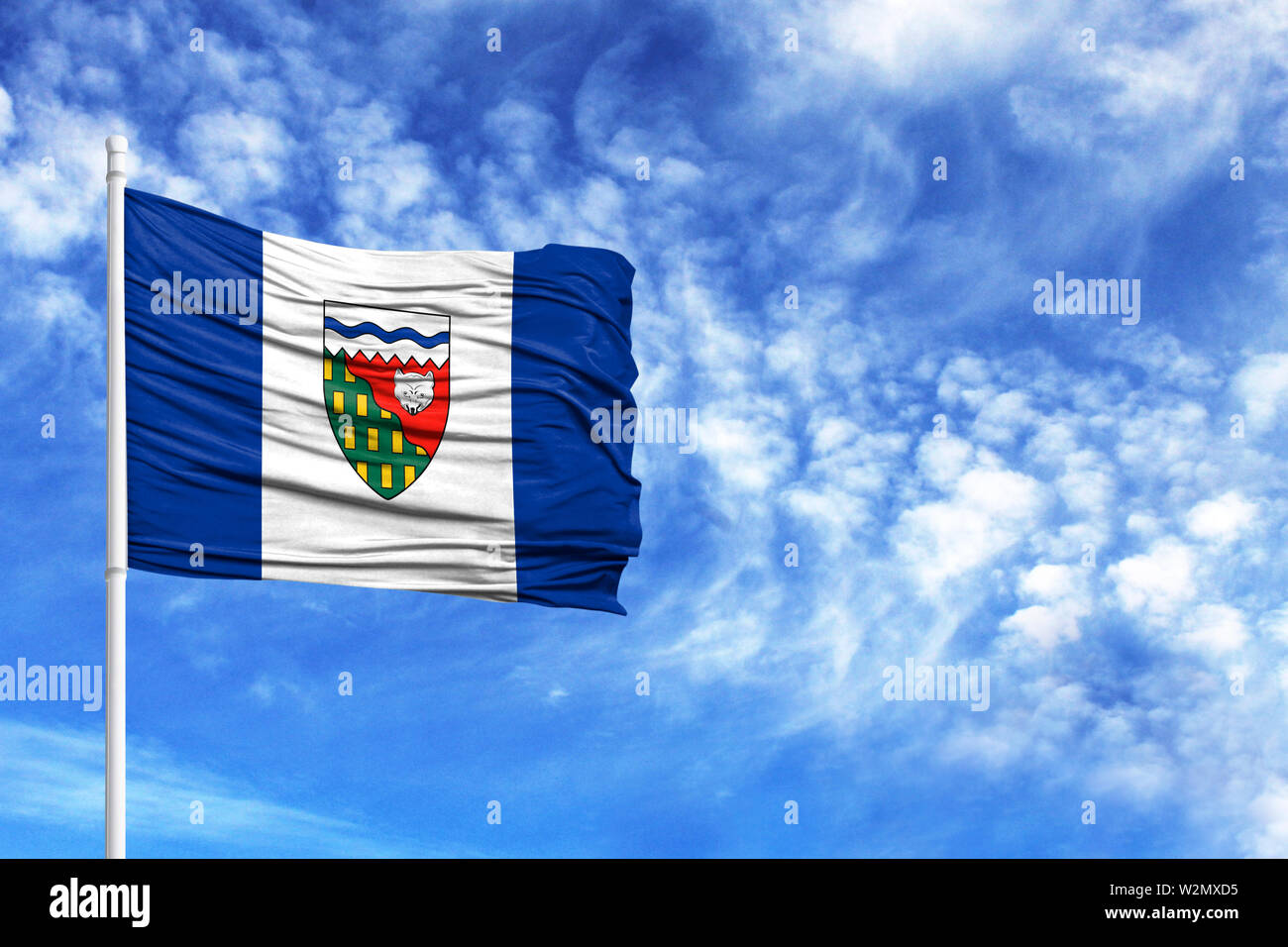 National flag of Northwest Territories on a flagpole in front of blue sky - Stock Image
